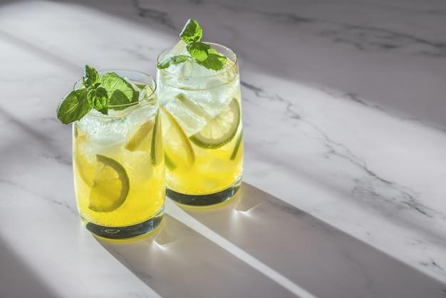 Deux verres de cocktail rafraîchissant avec citron vert et brins de menthe verte