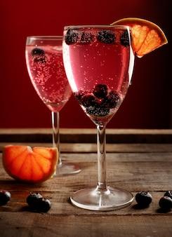Deux verres à cocktail rouge sur une table en bois rustique