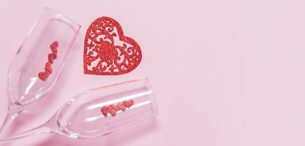 Deux verres et coeurs sur fond rose - date romantique pour le concept de la saint-valentin au format bannière