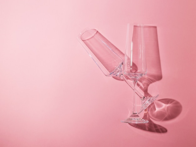 Deux verres en cristal sur de longues jambes sur fond rose. verrerie à la lumière dure.
