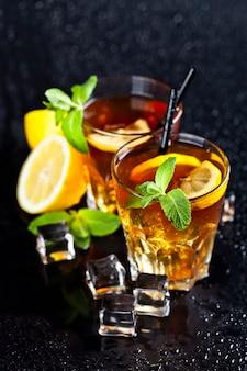 Deux verres avec du thé glacé traditionnel froid avec du citron, des feuilles de menthe et des glaçons.