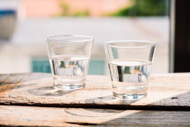 Deux verres d'eau sur table sur fond de bois