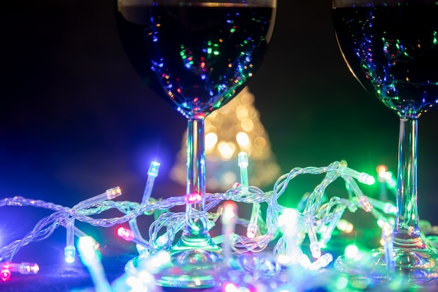 Deux verres sur fond d'arbre de noël brillant et une guirlande multicolore sur fond de nuit noire. célébration du nouvel an...