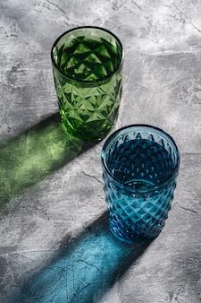Deux verres géométriques en verre avec de l'eau dans les couleurs bleues et vertes
