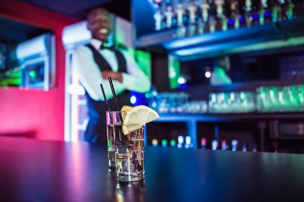 Deux verres de gin sur le comptoir et le barman se penchant