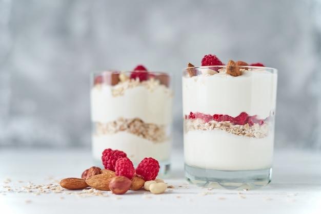 Deux verres de granola de yogourt grec avec des framboises, des flocons d'avoine et des noix sur un fond blanc.