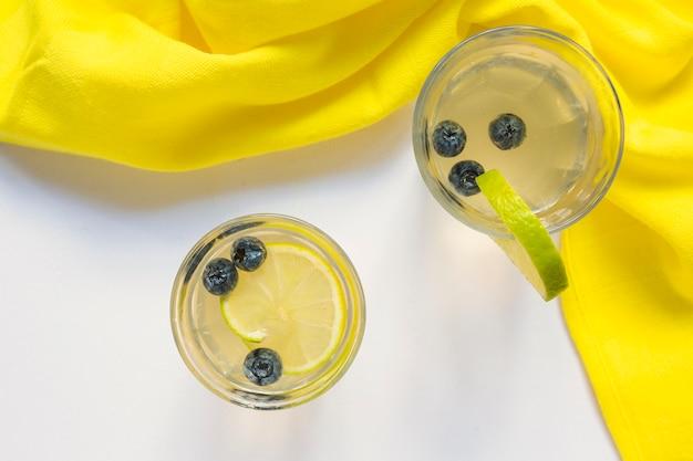 Deux verres de jus de citron avec des bleuets avec un tissu jaune sur fond blanc