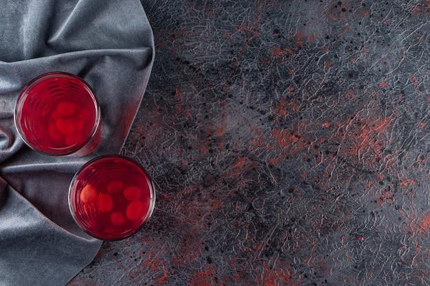 Deux verres de jus de fruits frais rouges placés sur une table en marbre.