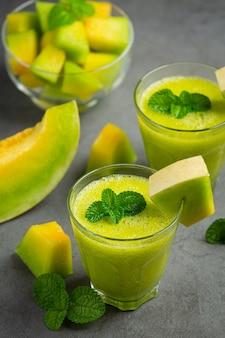 Deux verres de jus de melon mis sur un sol sombre