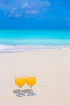 Deux verres de jus d'orange sur une plage blanche tropicale