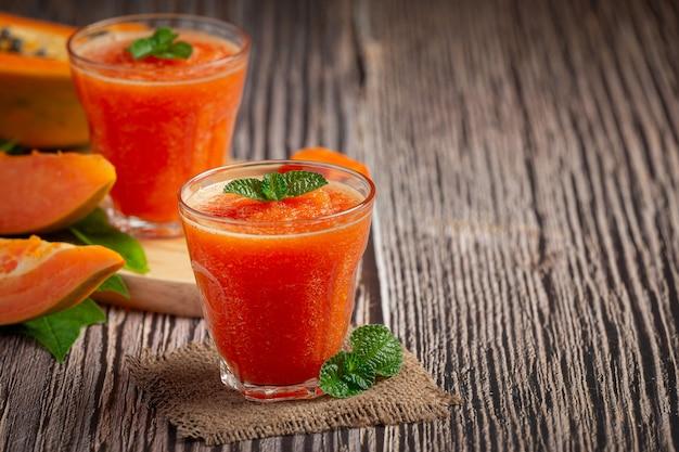 Deux verres de jus de papaye mis sur un plancher en bois
