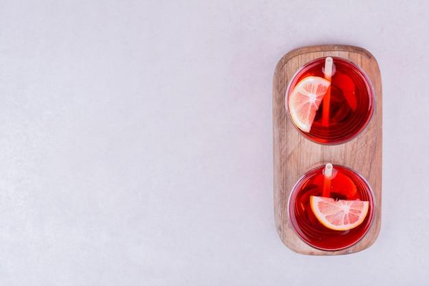 Deux verres de jus rouge sur une planche de bois