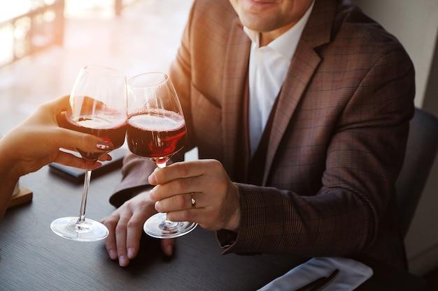 Deux verres de jus de vin rouge. un rendez-vous romantique, un homme et une femme trissent des lunettes.