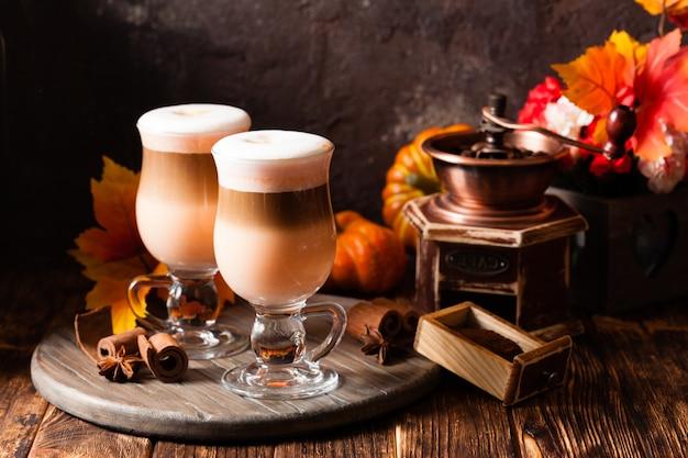 Deux verres de latte épicé à la citrouille avec de la crème fouettée et de la cannelle sur un support en bois