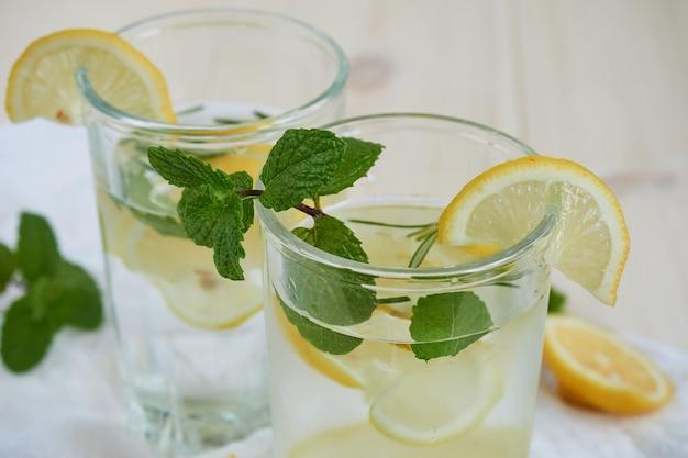 Deux verres de limonade fraîche au citron et à la menthe sur une serviette blanche, gros plan