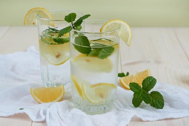Deux verres de limonade fraîche au citron et à la menthe sur une serviette blanche