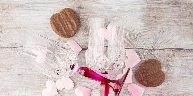 Deux verres à pied avec des coeurs et du chocolat. bannière