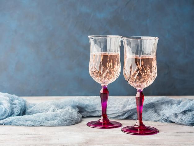 Deux verres à pied roses avec du champagne