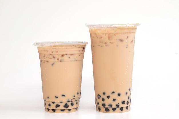 Deux verres en plastique de thé au lait glacé de taiwan avec bulle de boba, boisson sucrée grande et petite tasse en plastique sur fond blanc, concept de boisson et de nourriture