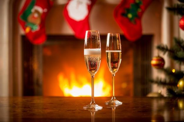 Deux verres remplis de champagne sur la table de noël devant la cheminée