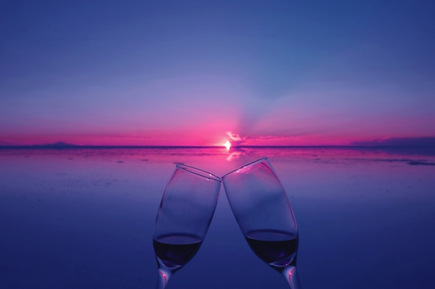 Deux verres retentissant pour célébrer le coucher de soleil après l'inondation des salines, uyuni, bolivie