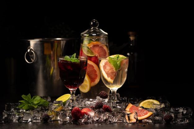 Deux verres de sangria au vin blanc et rouge avec des mûres, des fraises, du pamplemousse, du citron vert et des tranches d'orange avec de la glace et de la menthe