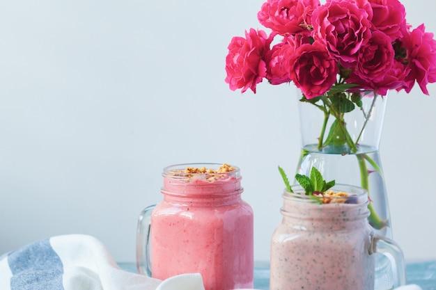 Deux verres de smoothie santé à la menthe fraîche sur la vieille table rustique en bois avec des fleurs roses fraîches