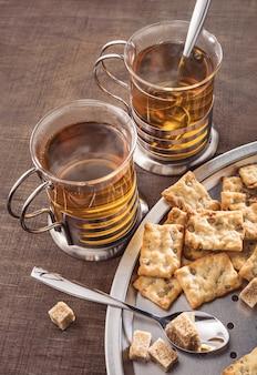 Deux verres de thé chaud et biscuits morceaux de sucre brun sur table sombre