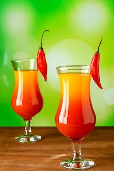 Deux verres en verre avec cocktail lever de soleil épicé dans un sur un bois sur fond vert vif.