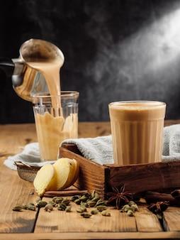 Deux verres en verre à facettes sur une table en bois avec la boisson indienne traditionnelle masala chai.