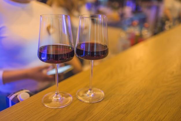 Deux verres à vin sur un bar avec une belle lumière ambiante.