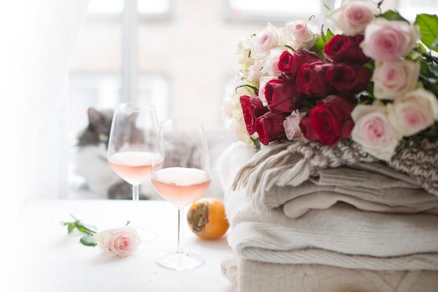 Deux verres de vin et beaucoup de vêtements chauds d'hiver à la maison près de la fenêtre. chat, grand bouquet de roses et de fruits d'automne dans le cadre. la ville est hors de la fenêtre. espace libre pour le texte.