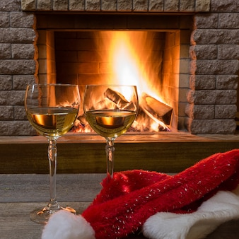 Deux verres à vin blanc et un chapeau de père noël de noël contre la cheminée