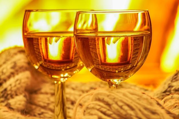 Deux verres de vin blanc et de choses en laine près de la cheminée.