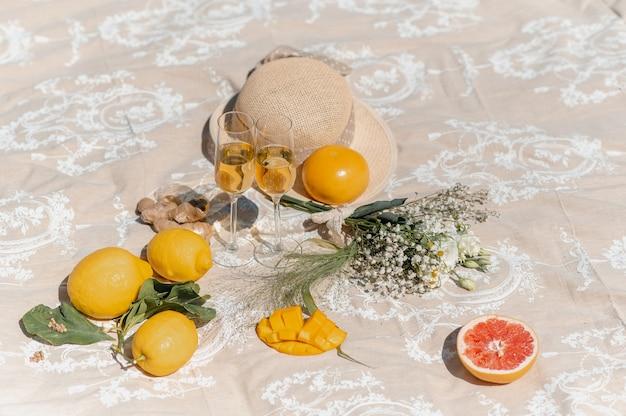 Deux verres à vin blanc sur une couverture avec des fleurs, un chapeau de paille et des fruits tropicaux autour.