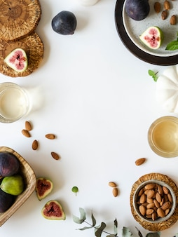 Deux verres de vin blanc, des figues et des amandes sur fond blanc.