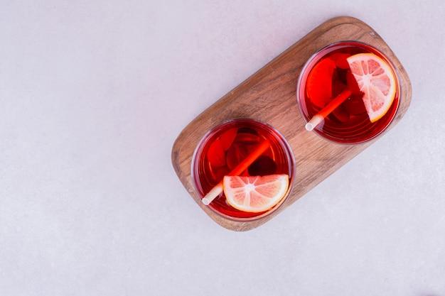Deux verres de vin brillant avec des tranches de citron.