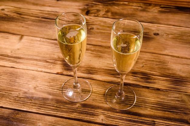 Deux verres à vin avec champagne sur table en bois rustique