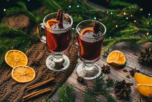 Deux verres de vin chaud sur une table en bois avec des branches de sapin nouvel an