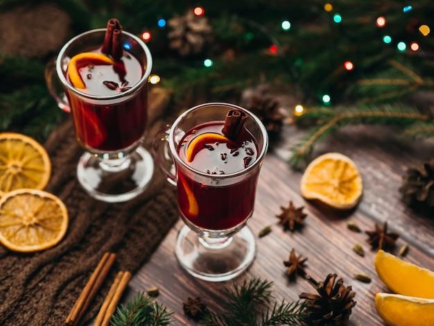 Deux verres de vin chaud sur la table avec des tranches d'orange et des épices