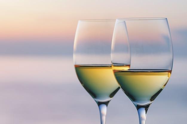 Deux verres de vin dans le contexte du soleil couchant avec copie espace