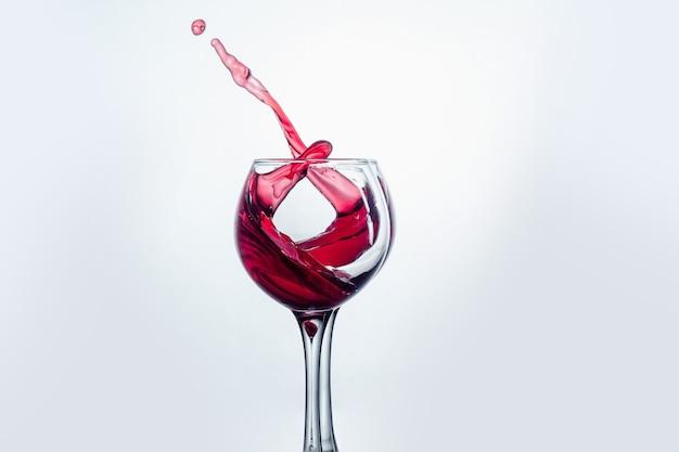 Deux verres à vin en geste de grillage avec de grandes éclaboussures au studio.