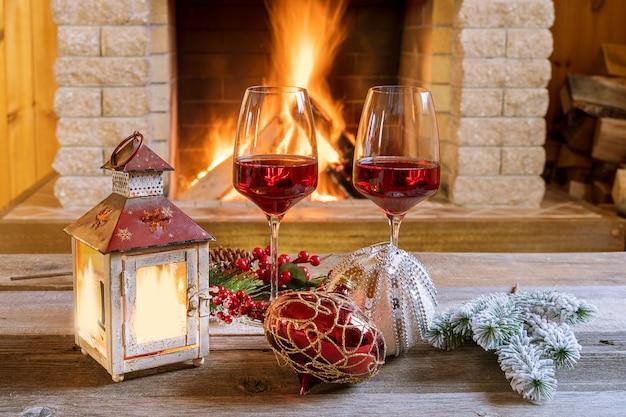 Deux verres de vin et lanterne de noël près d'une cheminée confortable dans une maison de campagne.