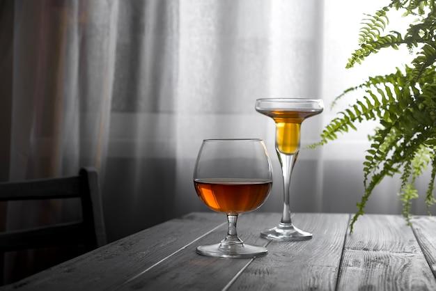 Deux verres de vin placés sur une table en bois sur le fond d'une fenêtre