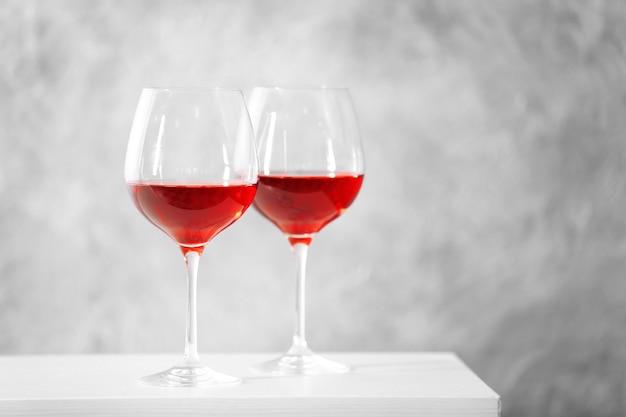 Deux verres de vin rouge avec des accessoires de noël sur la surface du mur gris