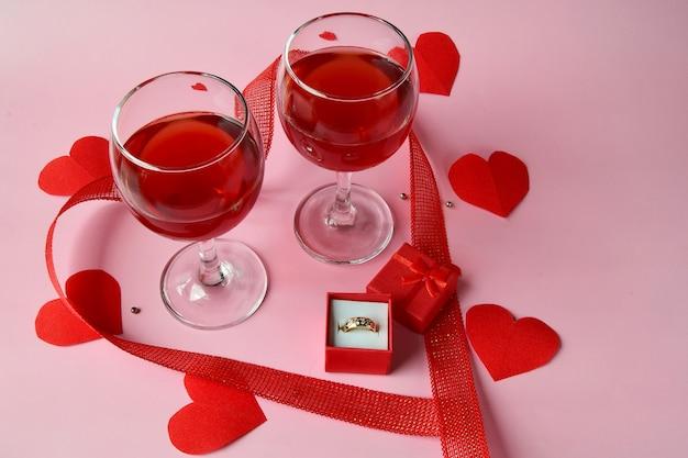 Deux verres de vin rouge avec un anneau dans une boîte cadeau rouge avec des coeurs rouges et un ruban sur fond rose