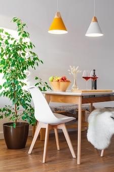 Deux verres à vin rouge bordeaux, bol en bois avec pommes vertes et rouges, vase décor sur table dans la cuisine