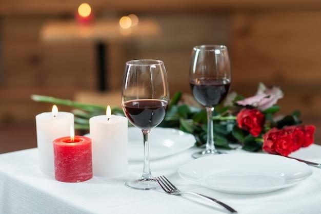 Deux verres de vin rouge, des bougies allumées et un bouquet de roses sur une table servie à l'intérieur.