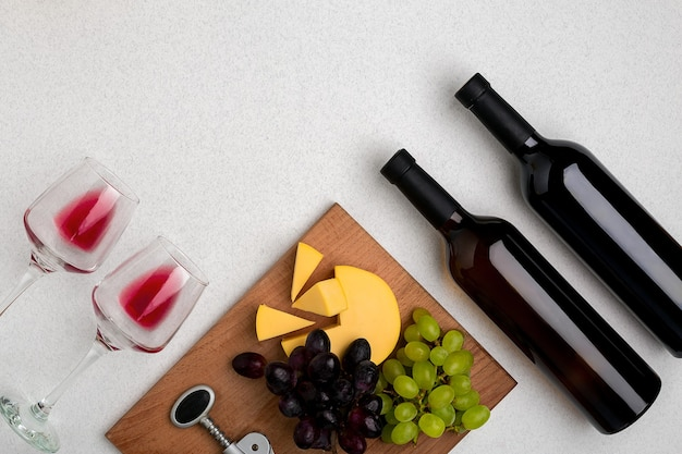 Deux verres de vin rouge, fromage et raisins vue de dessus