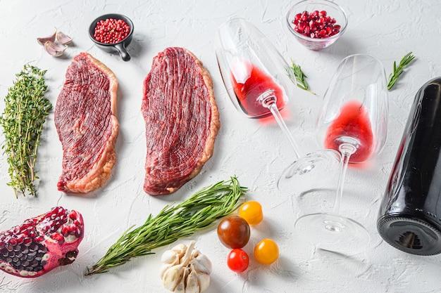 Deux verres de vin rouge près de la bouteille et des steaks de boeuf sur fond de béton blanc, vue latérale.